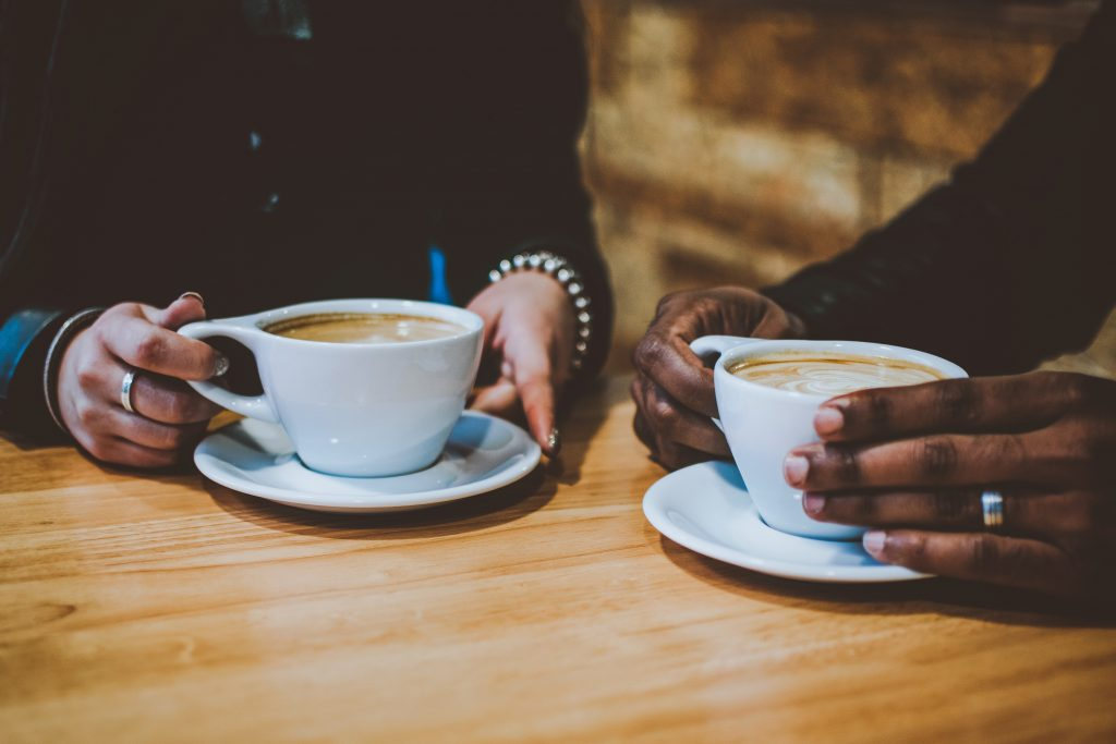 two people with hands holding coffee cups in a cafe