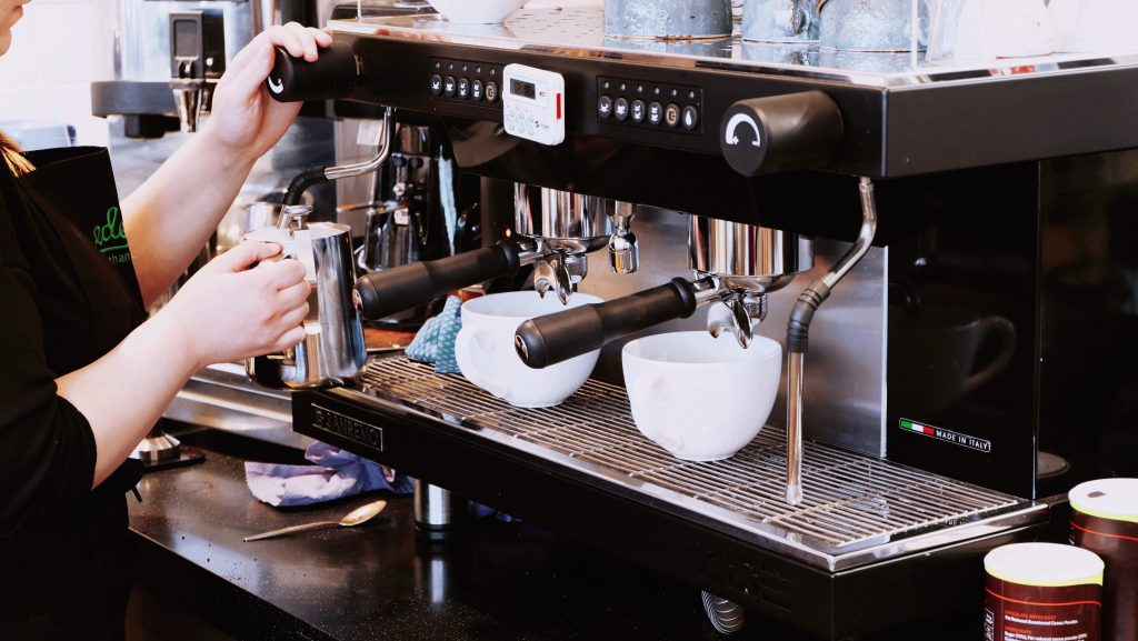 Barista using san remo espresso machine, steaming milk