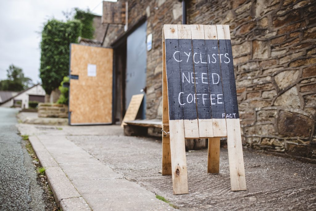 Cyclists need coffee written on wodden a-frame on street pavement.